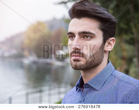 Portrait Of Contemplative Handsome Brown Haired Young Man, With Short Beard, Wearing Shirt Beside Pi