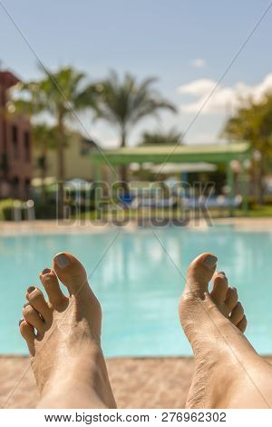 Beautiful Tanned Legs. Close-up Of Female Legs With A Swimming Pool On The Background. Beautiful Fem
