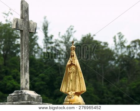 Scene In A Graveyard: Golden Statue Of Our Lady Of Aparecida, Widely Venerated By Brazilian Catholic