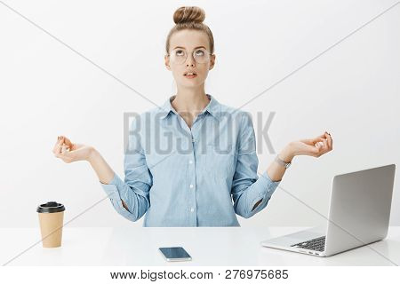 Woman Meditating In Office Sitting Near Table Having Break From Writing Article In Laptop, Drinking