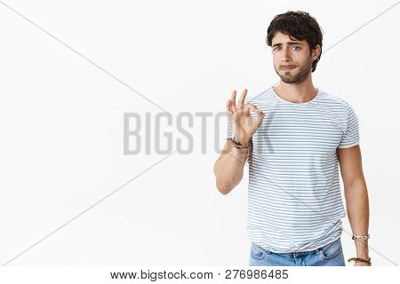 Studio Shot Of Pressured And Tired Unsure Young European Male Coworker Showing Okay Gesture While Pu