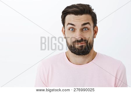 Close-up Shot Of Awkward Unsure Good-looking Caucasian Man With Beard Smirking Unsure And Silly Popp