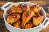 Baked glazed chicken drumsticks. Marinated in teriyaki, apricot jam, wine vinegar and corn starch sauce. White saucepan on  wooden rustic table poster
