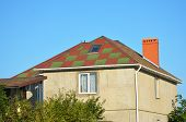 Incomplete house construction with colorful roof, attic skylight window, roof gutter, stucco walls. poster