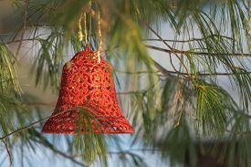 Sunlight Shines On Christmas Bell Ornament Outdoors Hanging On A Live Pine Tree In Winter.