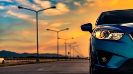 Blue Compact Suv Car Open Headlamp Light Parked On Concrete Road Near The Mountain At Sunset With Be