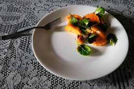 A Natural Shot Of An Orange And Basil Salad On A White Plate