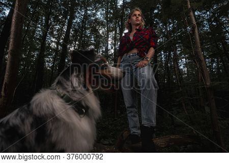 Aussie Australian Breed Dog With Beautiful Backpacker Woman Strolling And Hiking In Forest. Active L