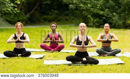 Multinational Young Girls In Sports Clothes Doing Yoga Meditation On Fresh Grass At Park, Panorama