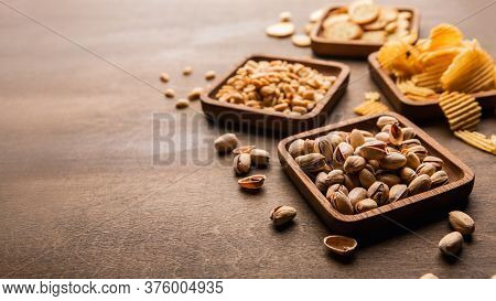 Rusks, Peanuts, Pistachios And Chips In Square Plates And Sprinkled On Brown Wooden Table In Pub