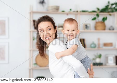 Happy Maternity. Young Mom Playing With Her Adorable Baby At Home, Piggybacking Him, Cute Child Laug