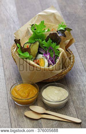 sabich: israeli pita sandwich with fried eggplant, hard boiled egg, israeli salad, amba and tahini souce
