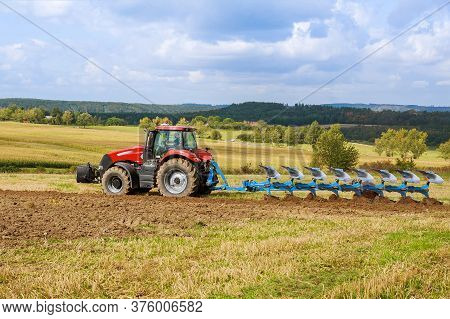 A Tractor With A Large Plow Plows A Field. Tractor With Agricultural Attachment.