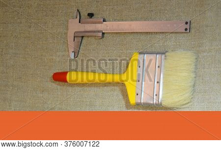 Tools For The Designer And Builder - A Wide Art Brush And A Vernier Caliper On A Tarpaulin Substrate