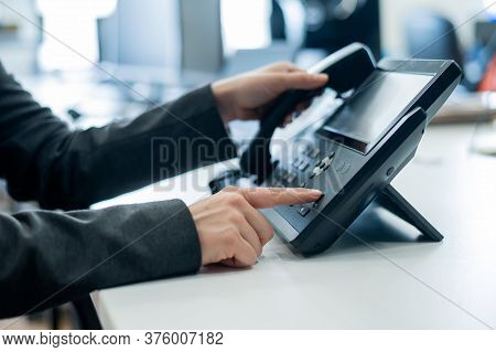 Closeup Female Hand On Landline Phone In Office. Faceless Woman In A Suit Works As A Receptionist An