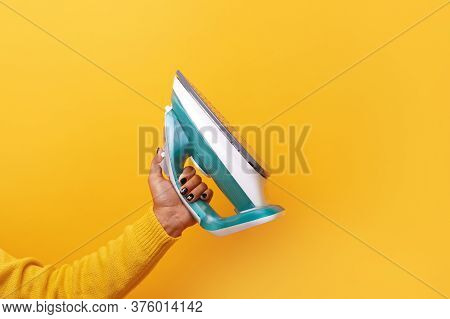 New Modern Iron In Hand Over Yellow Background
