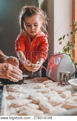 Grandmother And Granddaughter Sculpt Dumplings With Meat Filling.