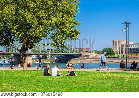 Cologne, Germany, August 23, 2019: People Tourists Walking Down And Having A Rest On Green Grass Law