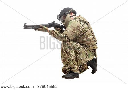 Military Commando In Uniform With A Shotgun Attacks And Aims On A White Isolated Background, Soldier