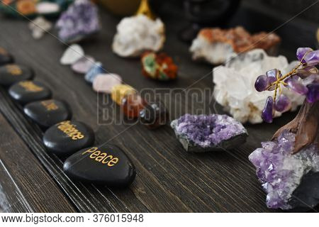 A Low Angle Image Of Black Polished Stones With Inspirational Messages And Chakra Healing Crystals O