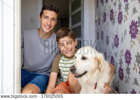 Two boys with a dog in doorway of their house