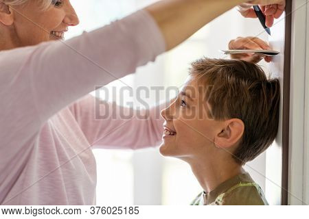Mother measuring the height of her son against wall at home