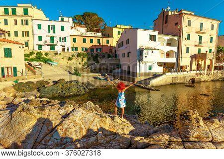 Happy Tourist Woman Enjoying Over Cliffs At Marciana Marina In Borgo Al Cotone, Elba Island, Italy F