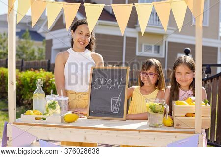 Cheerful young woman and little girl holding small noticeboard with picture of drink and open announcement while standing by stall
