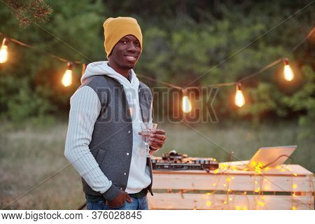 Happy young stylish African man with drink standing in front of camera against lights and table with stereo board during outdoor party