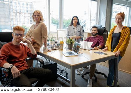 Group of intercultural business people in casualwear gathered by large table in office against window for discussion of strategies and ideas