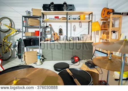 Interior of large contemporary garage for rehearsals with drum kit, acoustic guitar, bicycle and shelves with worktools and household stuff