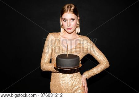 Pretty young elegant female with blond hair holding birthday cake covered by black marzipan with burning candle during celebration