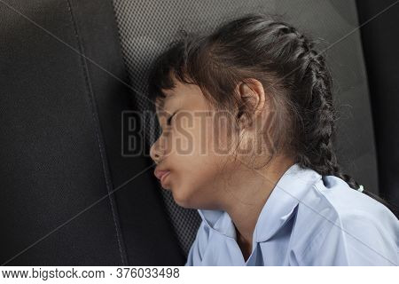 Asian Little Girl Sitting Asleep In The Car While Traveling To School.