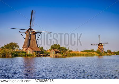 Netherlands Traveling. Traditional Dutch Windmill And House In Kinderdijk Village In The Netherlands