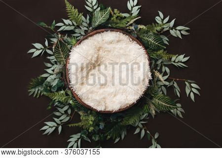 Newborn Digital Background - Brown Wooden Bowl With Green Leaves Wreath And White Faux Fur.