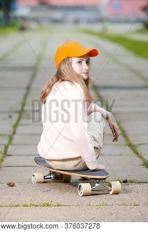Youth And Teenagers Lifestyle. Portrait Of  Positive Caucasian Teenager Girl Posing With Longboard I