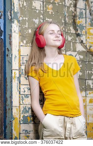 Youth And Teens Lifestyle. Dreaming Relaxing  Caucasian Teenager In Red Wireless Headphones Posing I