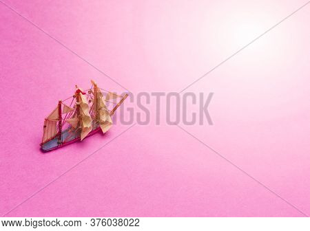 Travel Concepts. Scale Model Of Three-masted Sail Boat Placed Over Pink Background.horizontal Image