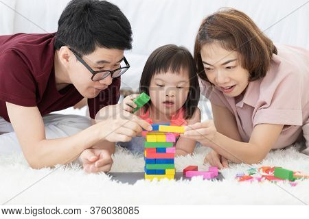 Little Girl With Learning Disabilities Or The Group Of Dow Syndrome Is Learning About Colorful Wood
