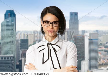 Portrait Of A Young Brunette Business Woman In Glasses Over City Background
