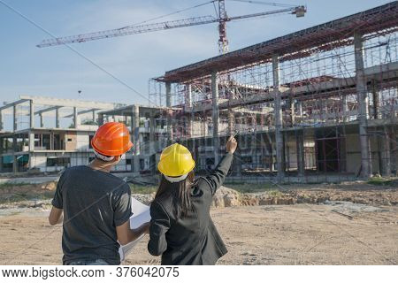 Professional Construction Woman Engineer Manager Wear Safety Yellow Helmet Point At Building Project