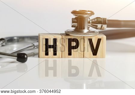 Hpv The Word On Wooden Cubes, Cubes Stand On A Reflective White Surface, On Cubes - A Stethoscope. M