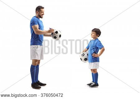 Full length profile shot of a footballer signing an autograph on a soccer ball for a junior football player isolated on white background
