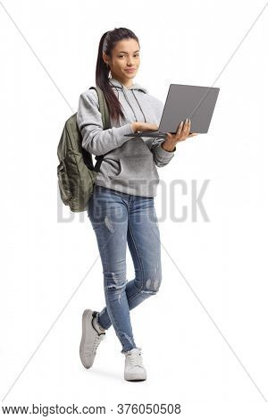 Full length portrait of a female student standing with a laptop computer and looking at the camera isolated on white background
