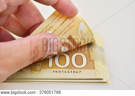 Close Up Shot Hand Counting One Hundred Canadian Banknote On White Background