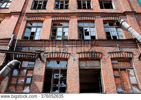 Wall Of Abandoned Building With Broken Windows. Old Red Brick House. Symbol Of Desolation And Loneli