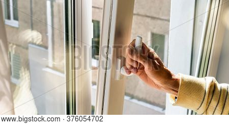 Old Man Hand Holds Plastic Window Handle To Open Vent Against City Building Outside In Street Closeu