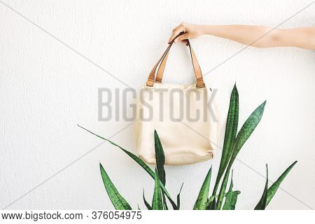 Hand Holding Eco Linen Bag For Food Or Shopping On White  Wall Background. Eco-friendly Concept Of C