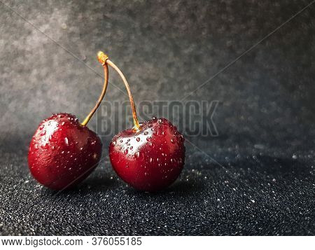 Bright Red Juicy Bold Cherry With A Trunk On A Black Heterogeneous Background With Drops Of Water.