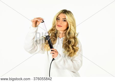 Form Exquisite Curls And Romantic Light Waves. Woman With Long Curly Hair Use Curling Iron. Hairdres